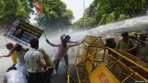 Indian Youth Congress are sprayed by a police water cannon