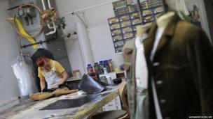 A woman works on a costume at the Art for Art costume workshop