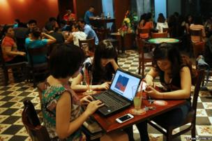 Three Vietnamese women use a laptop and smart phones at a cafe in Ha Noi, Viet Nam