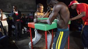 Arm wrestlers Mamadou Ba (L) and Cheikh Faye battle each other during a competition in the crowded Medina district of Dakar, Senegal, on 13 May 2013