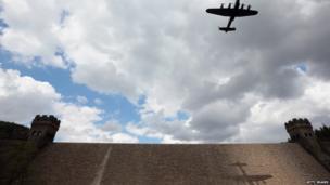 Lancaster bomber flying over dam