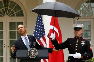 President Barack Obama checks to see if he still needs the umbrella held by a US Marine