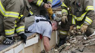 Rescue workers dig through the rubble of a collapsed wall at the Plaza Towers Elementary School in Moore