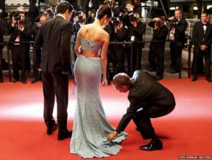 Director Takashi Miike adjusts the dress of cast member Nanako Matsushima as she poses on the red carpet with Takao Osawa at Cannes