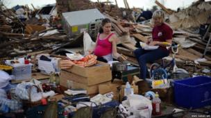 People eat their dinner amid the debris of their former home in Moore, Oklahoma
