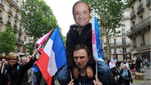 Anti-gay marriage protester wearing Francois Hollande mask sits on shoulders of another protester waving French flag.