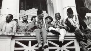 Tenzing and Hillary wearing chains of flowers and sitting on a balcony