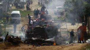 Firefighters try to extinguish a burning vehicle during clashes between Buddhist and Muslims in Lashio