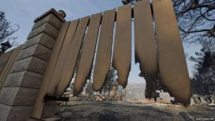 The remains of a home is seen through a burnt fence after the home was destroyed by the Powerhouse wildfire in Lake Hughes, California