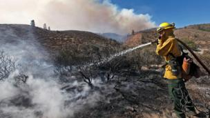 A firefighter holds a hose over scorched earth near Los Angeles, California 3 June 2013