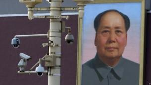 A portrait of late Chinese leader Mao Zedong is displayed near security cameras on the eve of the 24th anniversary of the bloody military crackdown on protesters near Tiananmen Gate in Beijing 3 June 2013