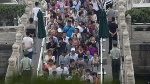 Visitors walk past the plain clothes policemen and paramilitary policemen as they enter Tiananmen Gate in Beijing 4 June 2013