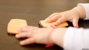 Toddler reaching for biscuits