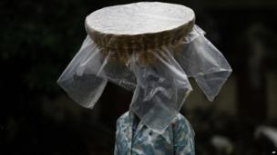 A fish vendor carries his basket on his head covered with plastic as he walks through a street during monsoon rains in Mumbai, India, on Sunday, June 9, 2013. The Southwest monsoon, arrived in the city Saturday, three days ahead of schedule, according to the meteorological department