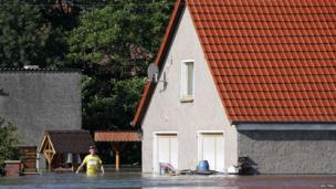 Man wades in front of his house in Kabelitz, north of Magdeburg, Germany, 10 June 2013