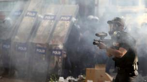 Police officer fires rubber bullets in Taksim Square, Istanbul, on 11 June 2013