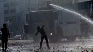 A protester throws a stone at a water cannon vehicle during clashes with riot police in Istanbul's Taksim Square on 11 June 2013