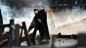 Protesters shield themselves from water cannons during clashes with riot police in Istanbul's Taksim square