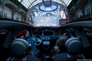 Visitors watch a film as they attend the opening night of a drive-in cinema at the Grand Palais in Paris
