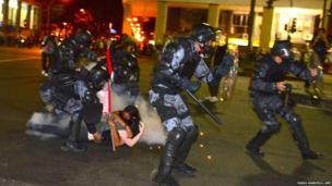 A couple embrace each other as riot police pass them