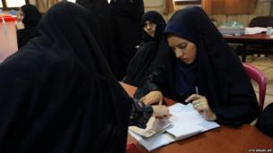 Iranian women register before casting their vote during the first round of the presidential election at a polling station in Tehran