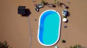 A garden with a swimming pool is inundated by the waters of the Elbe river during floods near Magdeburg