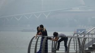 A couple having their wedding photos taken in front of the hazy skyline of Singapore 17 June 2013
