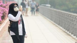 A woman wearing a face mask uses a mobile phone as Singapore suffered a second day blanketed in a thick haze on 18 June 2013