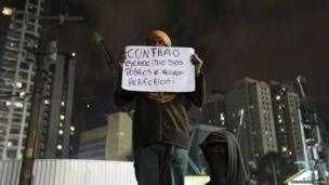 """A protestor in Sao Paulo holds up a banner reading: """"Against the genocide of the poor and blacks of the suburbs!"""", 17 June 2013"""
