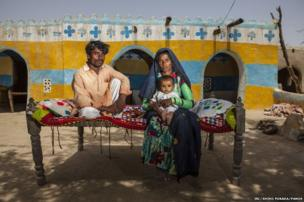 From left to right: Haryoo, Tarjan, holding their son Peeriyo, 8 month, in District Umerkot, Sindh province, Pakistan, April 10, 2013.