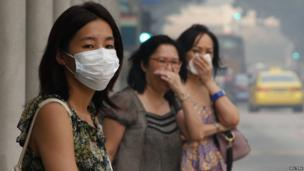 Commuters cover their mouths as they wait to cross a road in the haze in Singapore on 20 June 2013