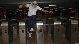 Protester jumps over a turnstile during public transport protest, Brasilia (19 June)