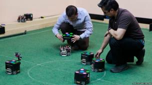 Colombia's engineers from Bogota's Santo Tomas University prepare robots during a training session of the robot football team