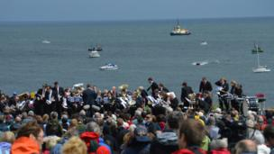 Brass band, crowds and vessels taking part in Foghorn Requiem
