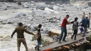 Indian army personnel help stranded people cross a flooded river after heavy rains in the Himalayan state of Uttarakhand 23 June 2013