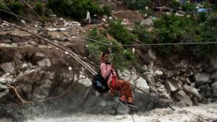 A stranded Indian pilgrim is transported across a river using a rope rescue system by Indo-Tibetan Border Police (ITBP) personnel in Govind Ghat on 23 June 2013