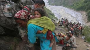 Soldiers assist a woman carrying a child on her back during rescue operations in Govind Ghat in the Himalayan state of Uttarakhand on 23 June 2013