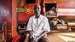 Maliki S Kamara sits in front of a fire engine