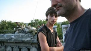 Father and son stand next to a Russian armoured vehicle during the 2008 conflict between Georgia and Russia.