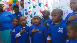 A choir of children dressed in identical blue shirts from the Thand Uxolo Day Care centre in Pretoria sings for Mr Mandela, their hands against their hearts