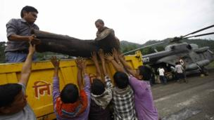 Locals unload a piece of wood from a truck to be placed on to an Indian Air force helicopter as cremation efforts for those killed in landslides and monsoon floods get underway, in Gauchar, Uttarakhand