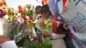 Mr Mandela's relatives hold flower bouquets (27 June 2013)