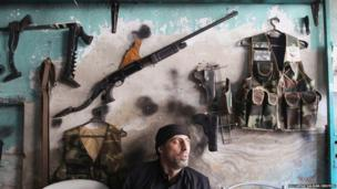 A customer sits near weapons displayed at Abu Mohammad's gun shop in the city of Aleppo, Syria