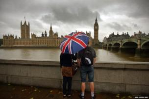 Tourists take in the view on the banks of the River Thames