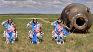 Zhang Xiaoguang, Nie Haisheng and Wang Yaping salute after returning to Earth