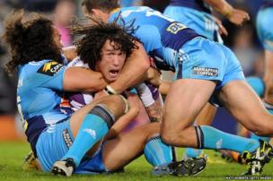 Kevin Proctor of Melbourne Storm is tackled during an Australian Rugby League match against the Gold Coast Titans