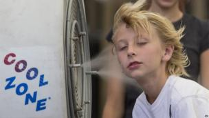A boy stands in front of a misting fan in Mesa, Arizona (28 June 2013)