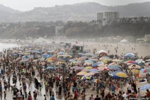 A large crowd of people gather at Santa Monica Beach in Santa Monica, California