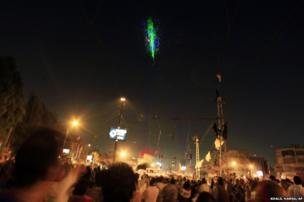 Opponents of Egypt's Islamist President Mohammed Morsi look at a military helicopter lit up by protesters' laser pointers