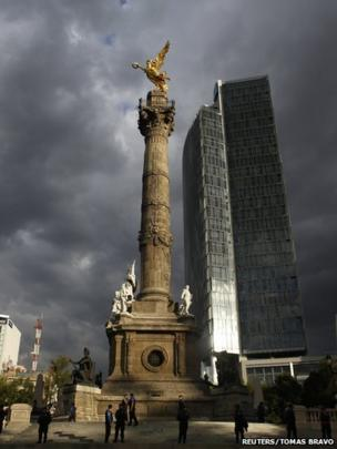 Police officers stand guard at the Angel of Independence monument before a protest against the privatisation of the state oil monopoly Pemex in Mexico City, 1 July